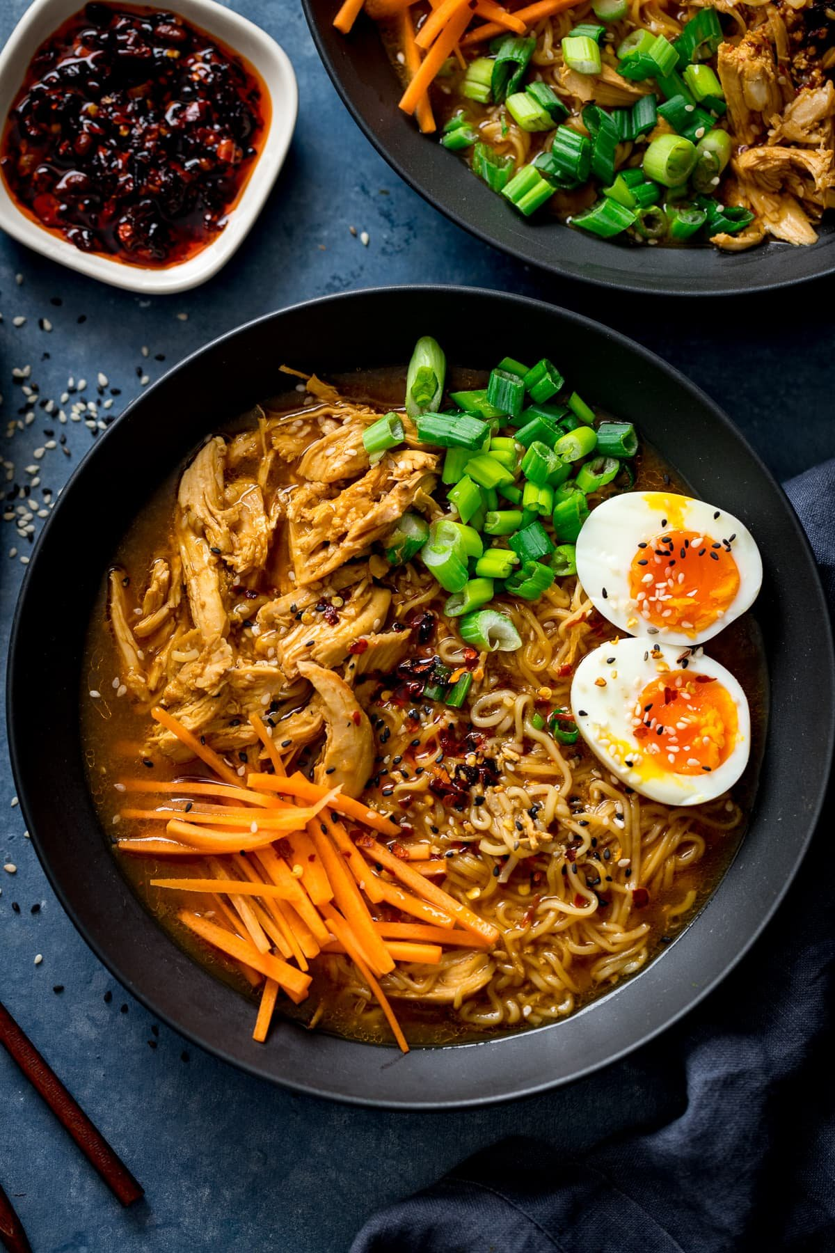 Overhead of chicken ramen in a black bowl with toppings of egg, spring onions and carrot strips.