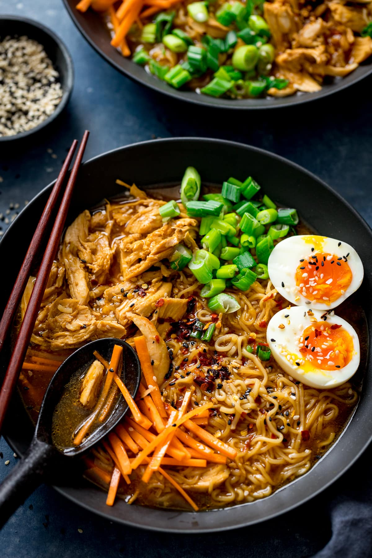 Chicken Ramen in a black bowl topped with egg, carrots and spring onions. Spoonful being taken.