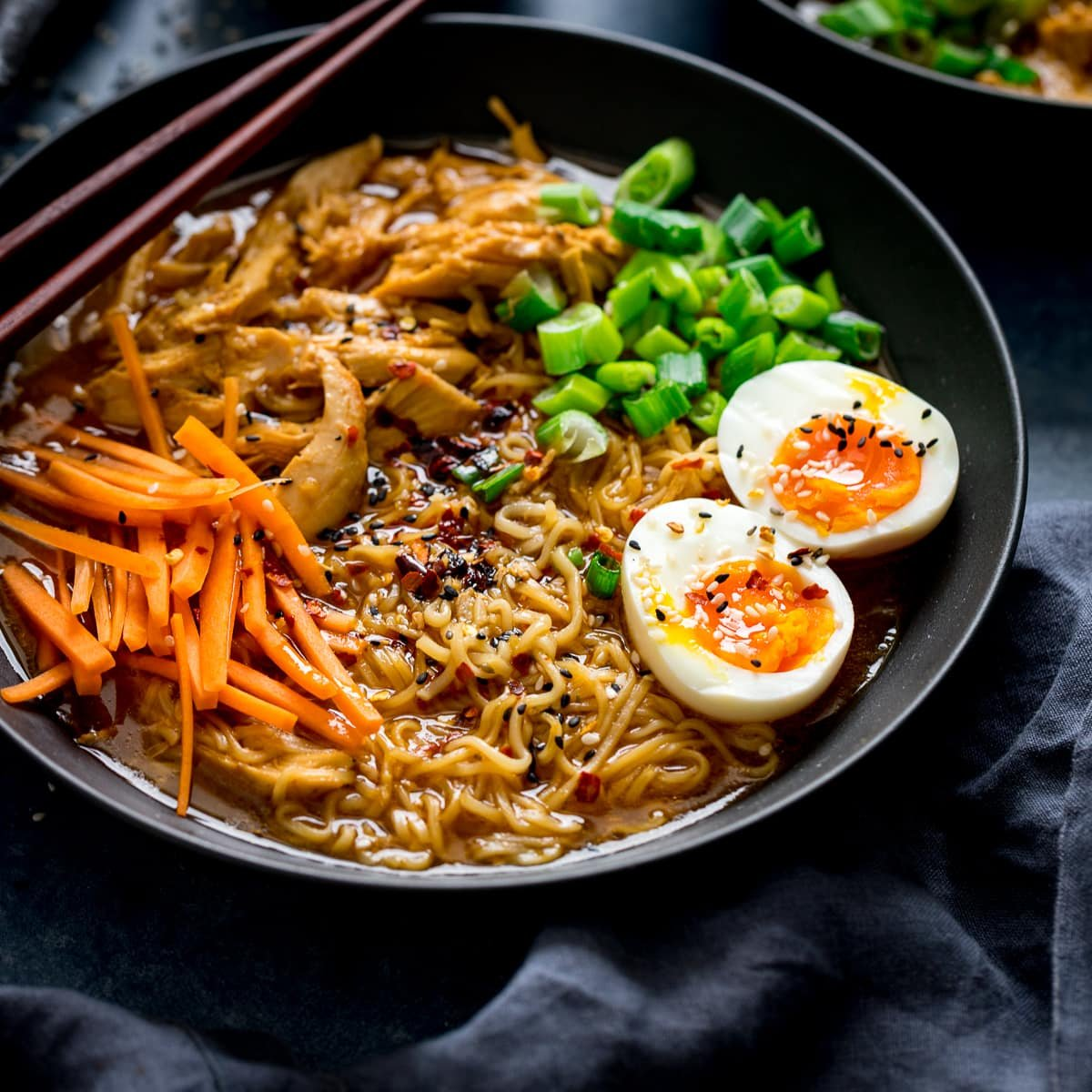 Chicken Ramen in a black bowl topped with egg, carrots and spring onions