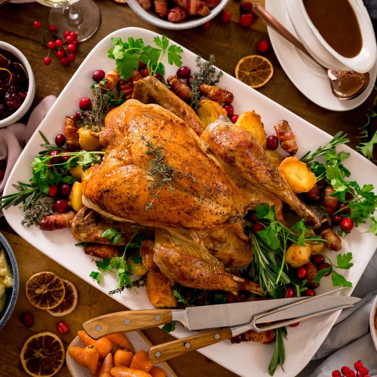 Roast turkey on a white plate surrounding by garnishings of herbs, cranberries and Christmas dinner side dishes