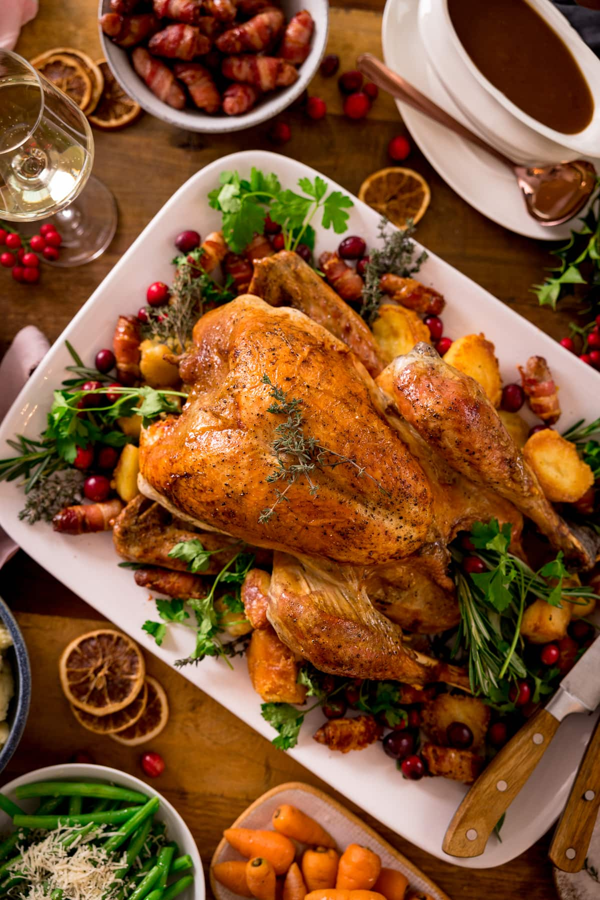 Roast turkey on a white rectangular plate surrounded by side dishes.