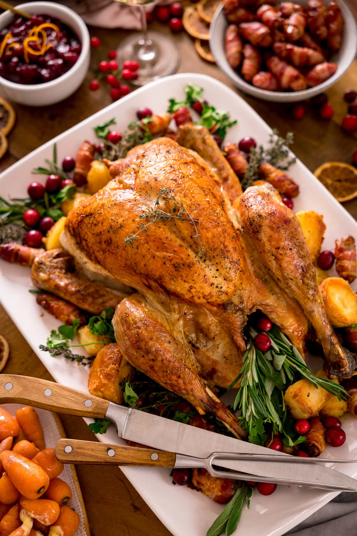 Roast turkey on a white plate with herbs, side dishes and a carving knife and fork on the plate.