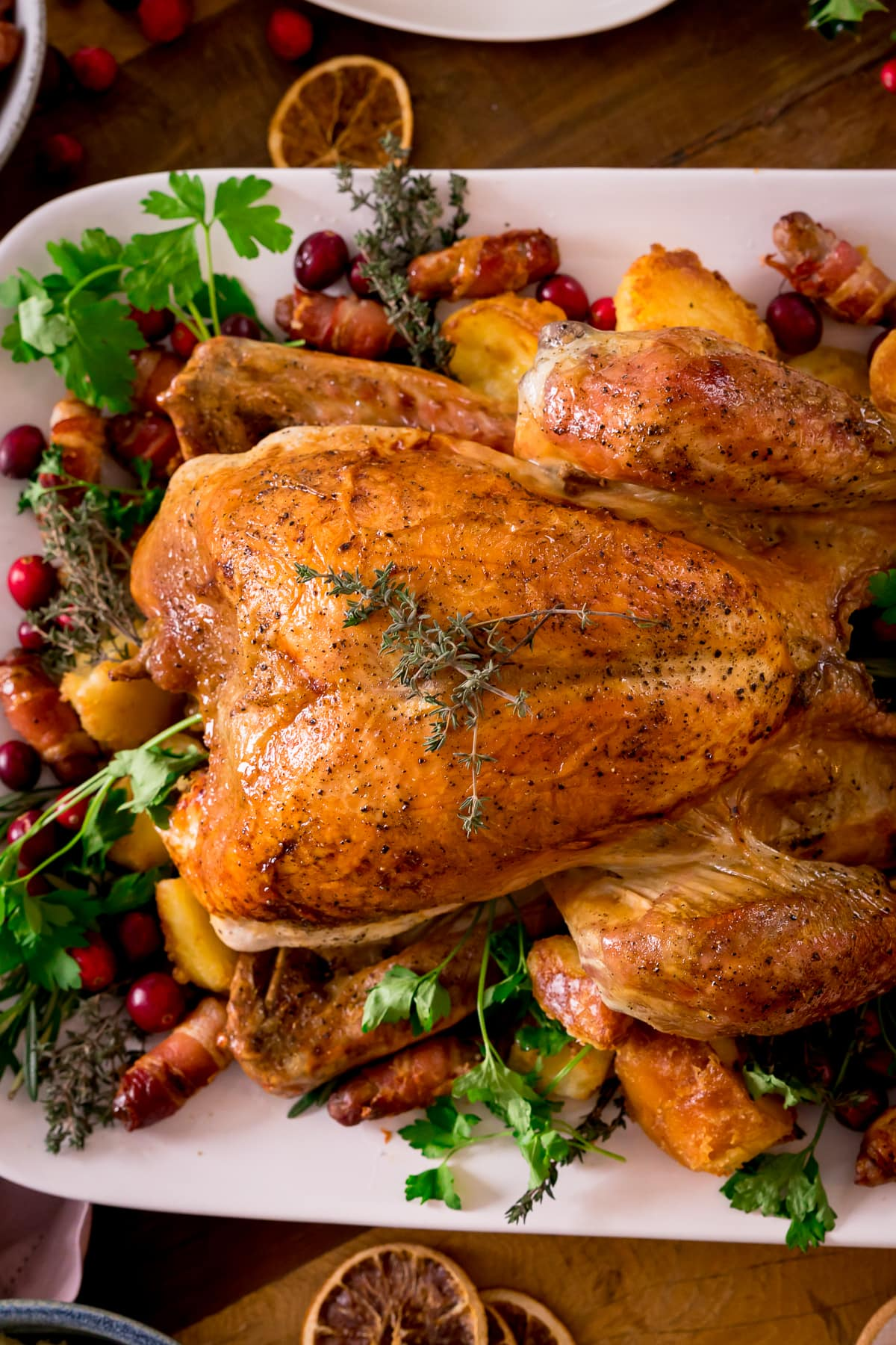 Roast turkey on a white plate surrounded by fresh herbs, cranberries and other garnishes.