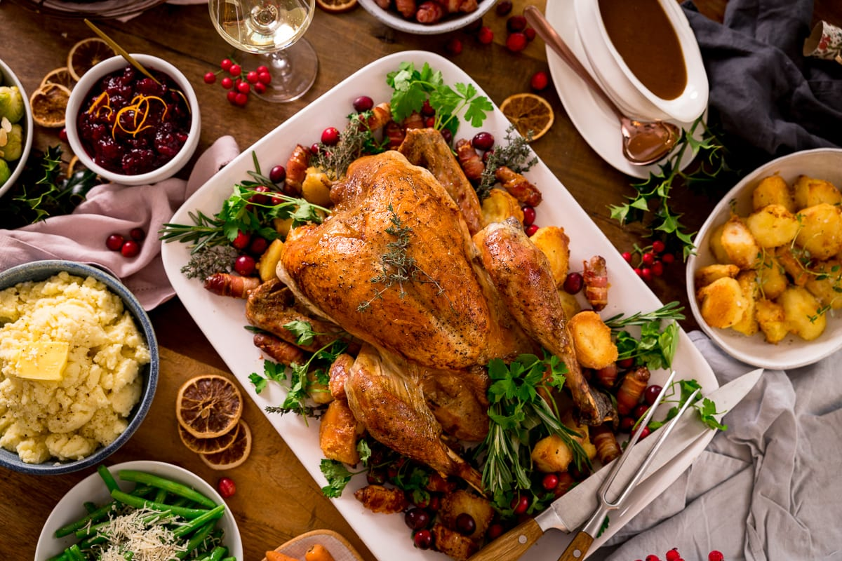 Roast turkey christmas dinner with vegetables and gravy on a wooden table.