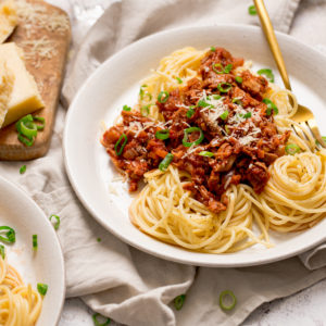 leftover turkey bolognese on a white plate with spaghetti