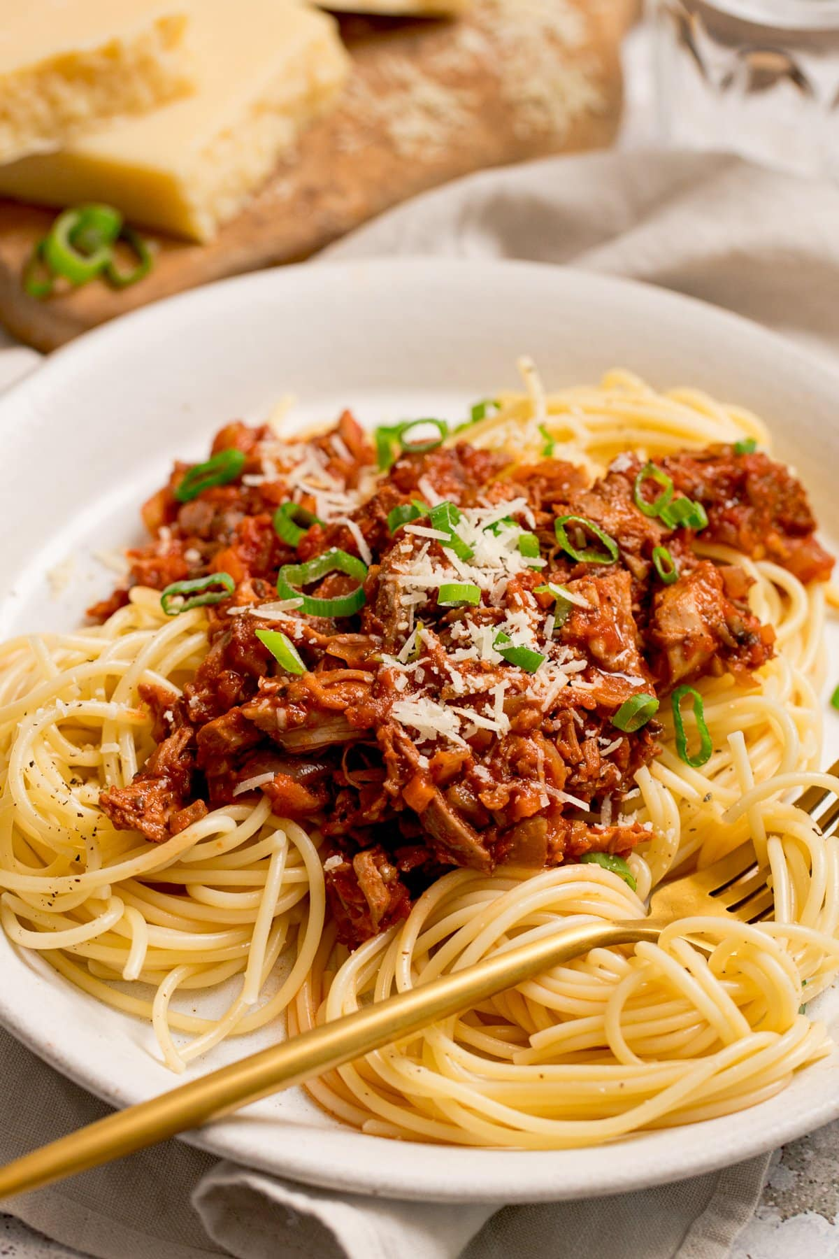 leftover turkey bolognese on a white plate. Gold fork resting on the plate.