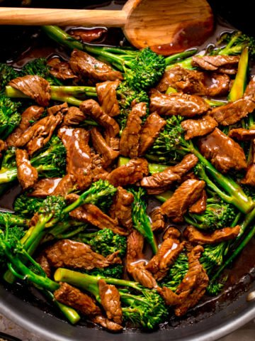 beef and broccoli stir fry in a pan with a wooden spoon