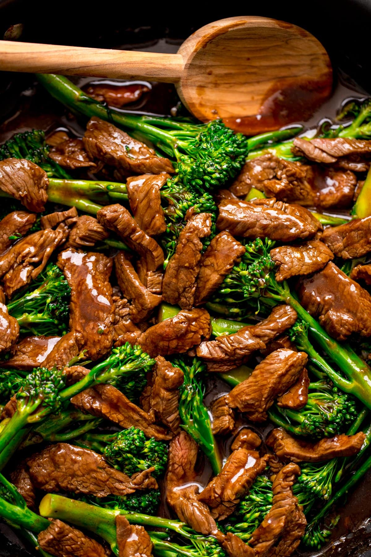 Close up overhead image of Chinese beef and broccoli in a pan with a wooden spoon.