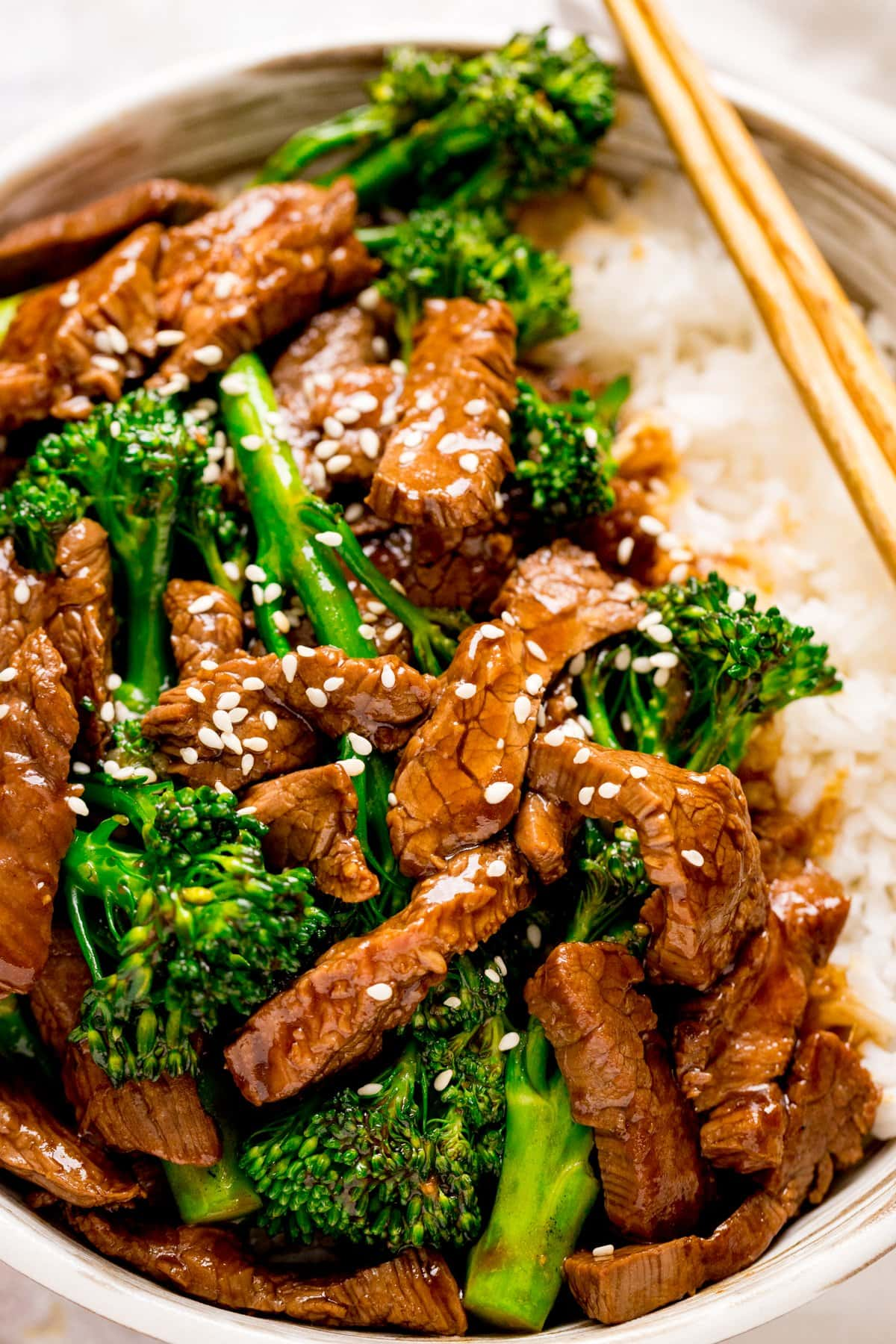 beef and broccoli topped with sesame seeds in a bowl with rice. Chopsticks resting on bowl.