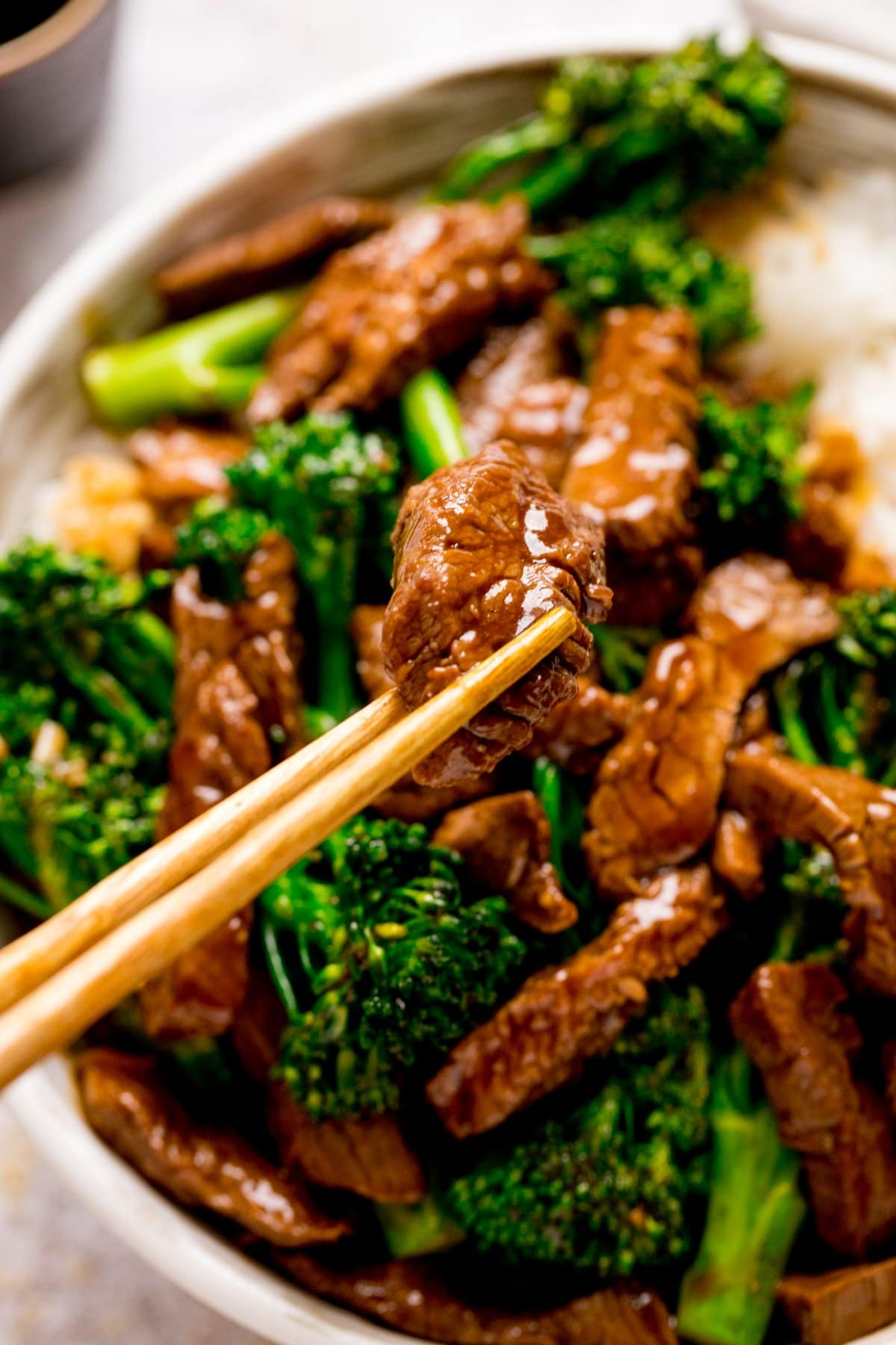Chopsticks taking a piece of Chinese beef from a bowl of beef and broccoli.