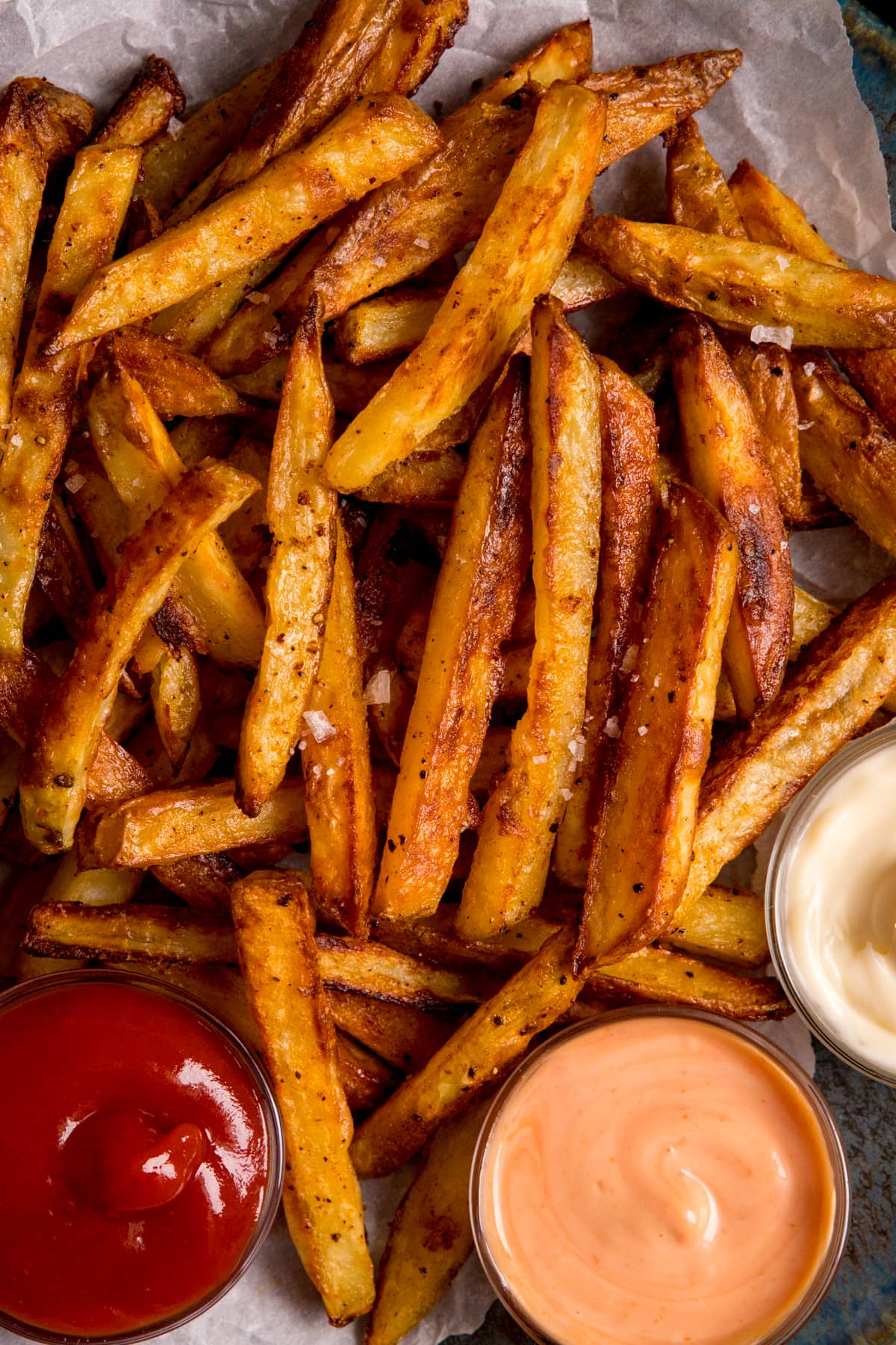Close up overhead image of crispy oven fries with a selection of sauces on baking parchment.