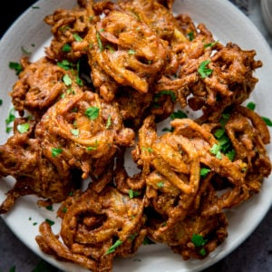Onion bhajis on a white plate, sprinkled with coriander.