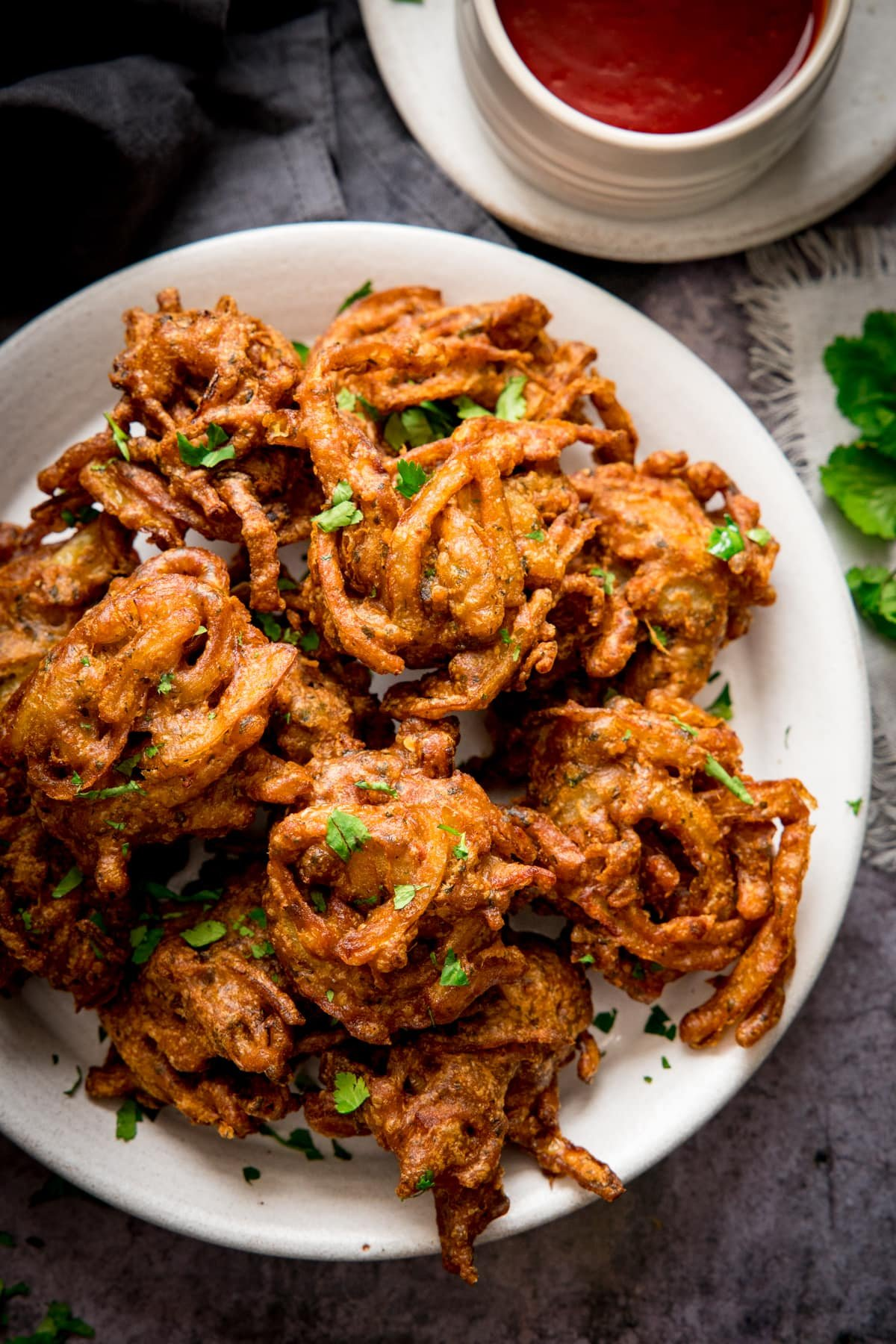 Onion bhajis on a white plate. Small white bowl filled with chilli sauce just in shot.