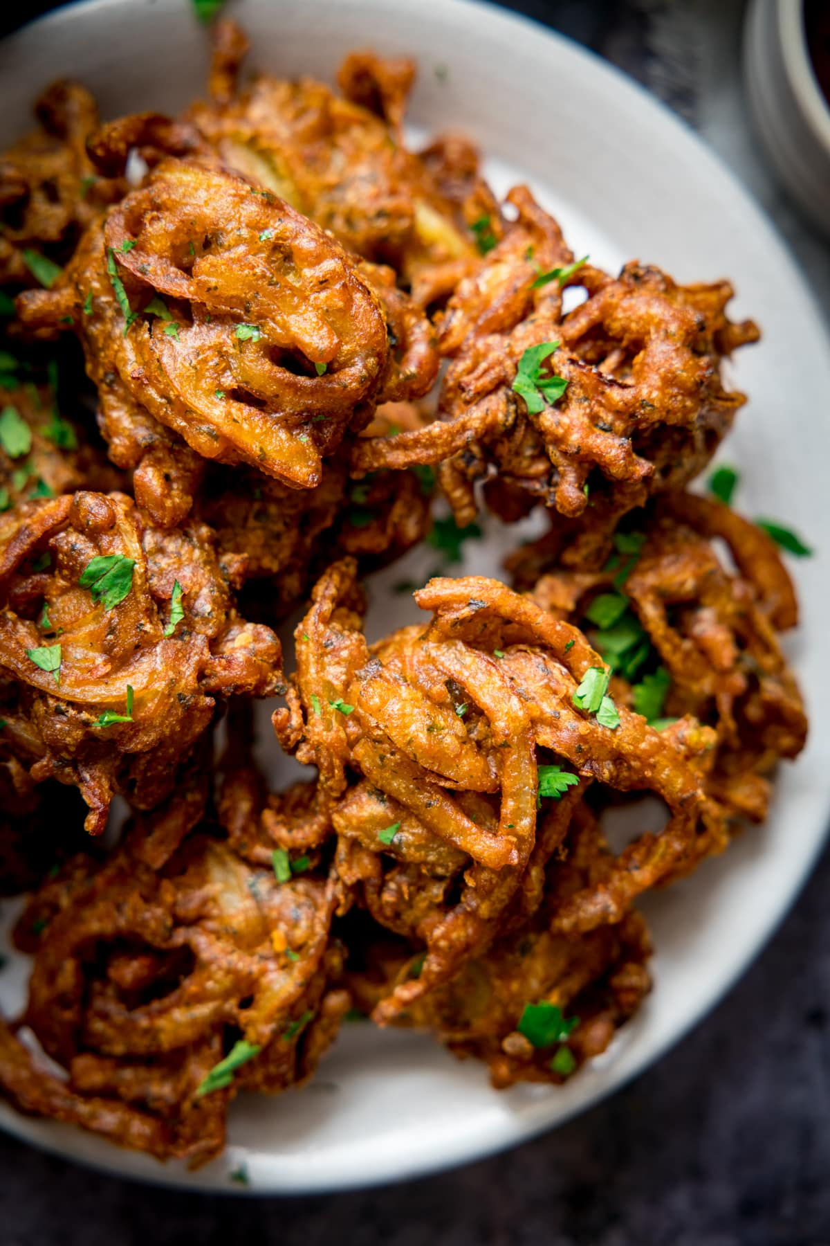 Overhead of Onion bhajis on a white plate.