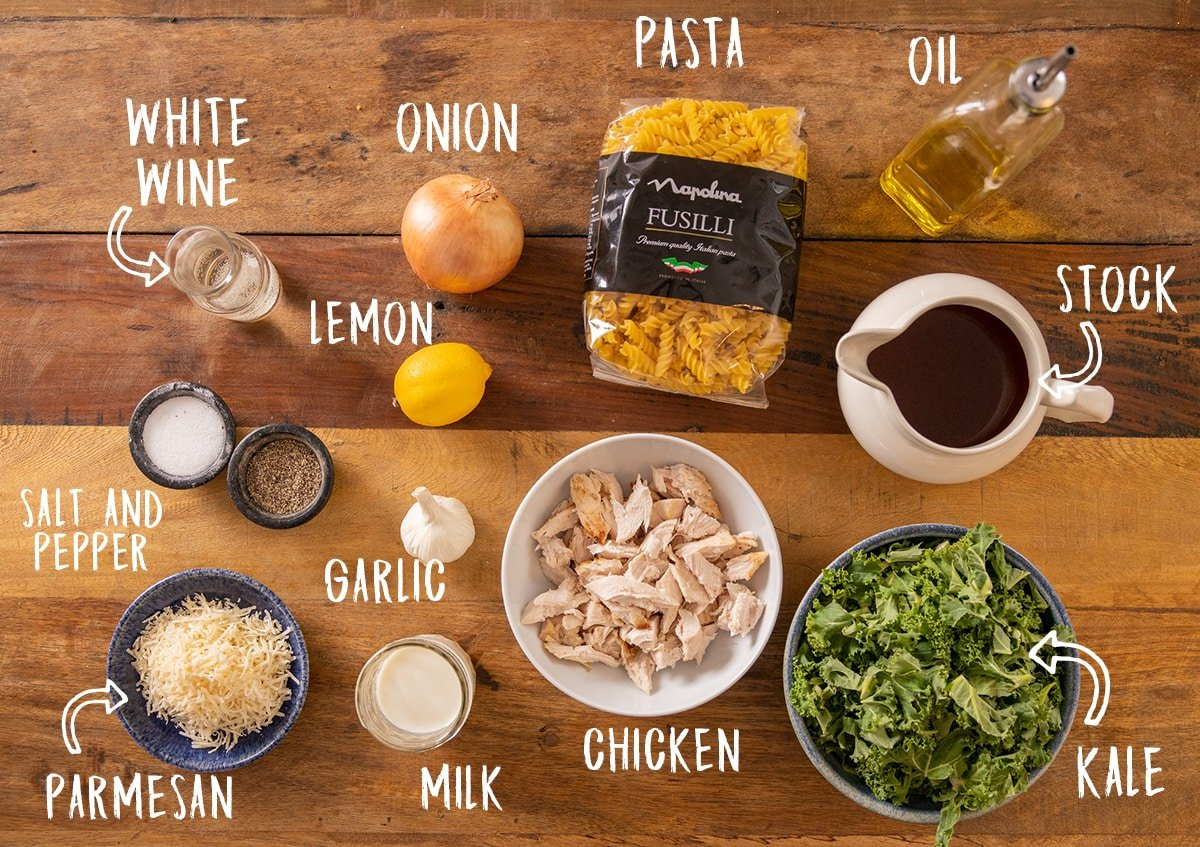 Ingredients for a one pot chicken pasta recipe laid out on a wooden table with titles superimposed on.