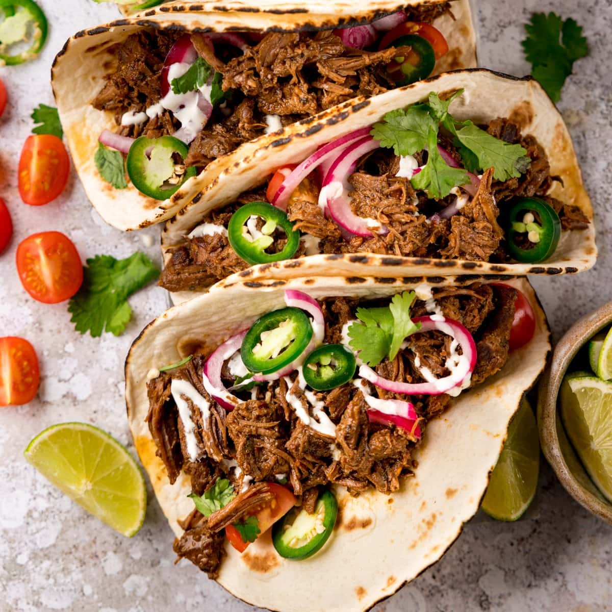 Square image of beef barbacoa on soft tacos topped with red onion and jalapeno slices