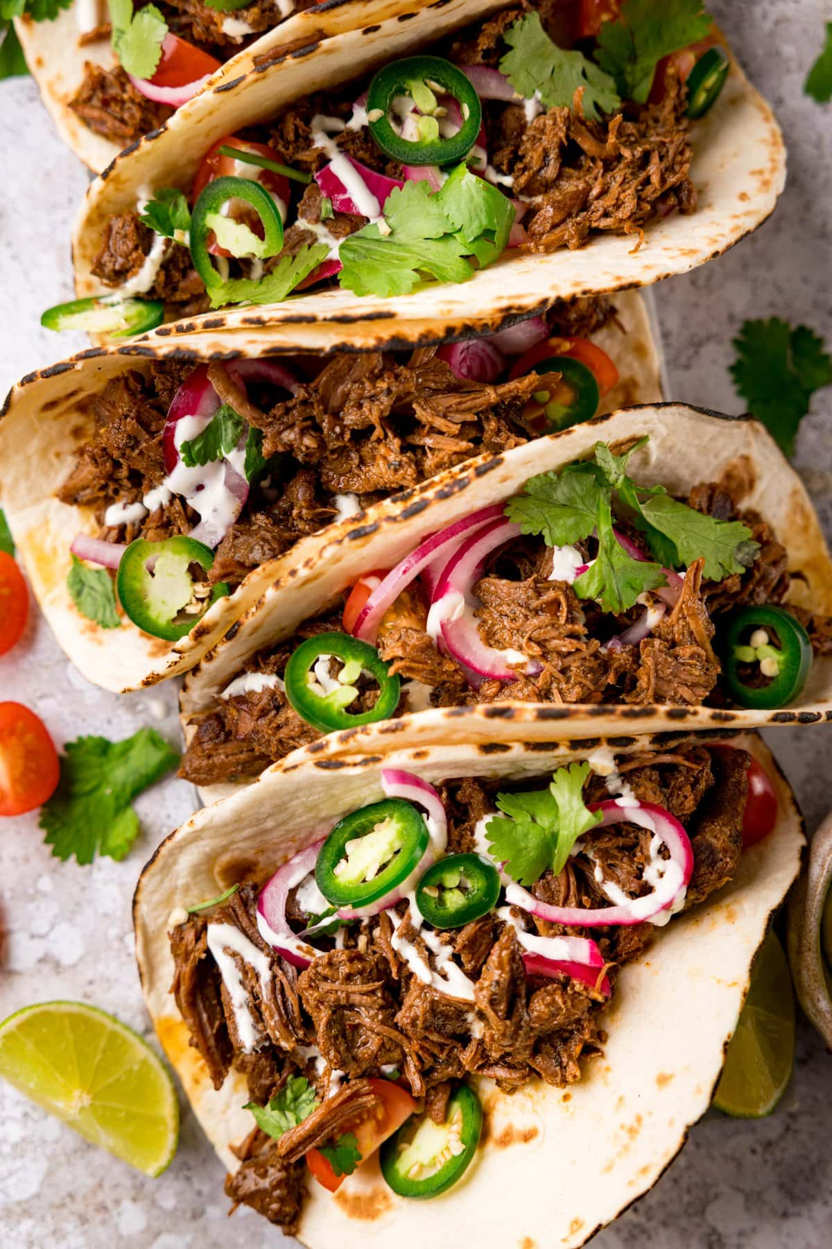 Overhead image of beef barbacoa tacos lined up on a light background