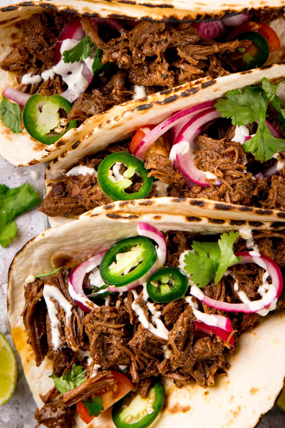 Close up overhead shot of beef barbacoa tacos topped with jalapeno and red onion slices