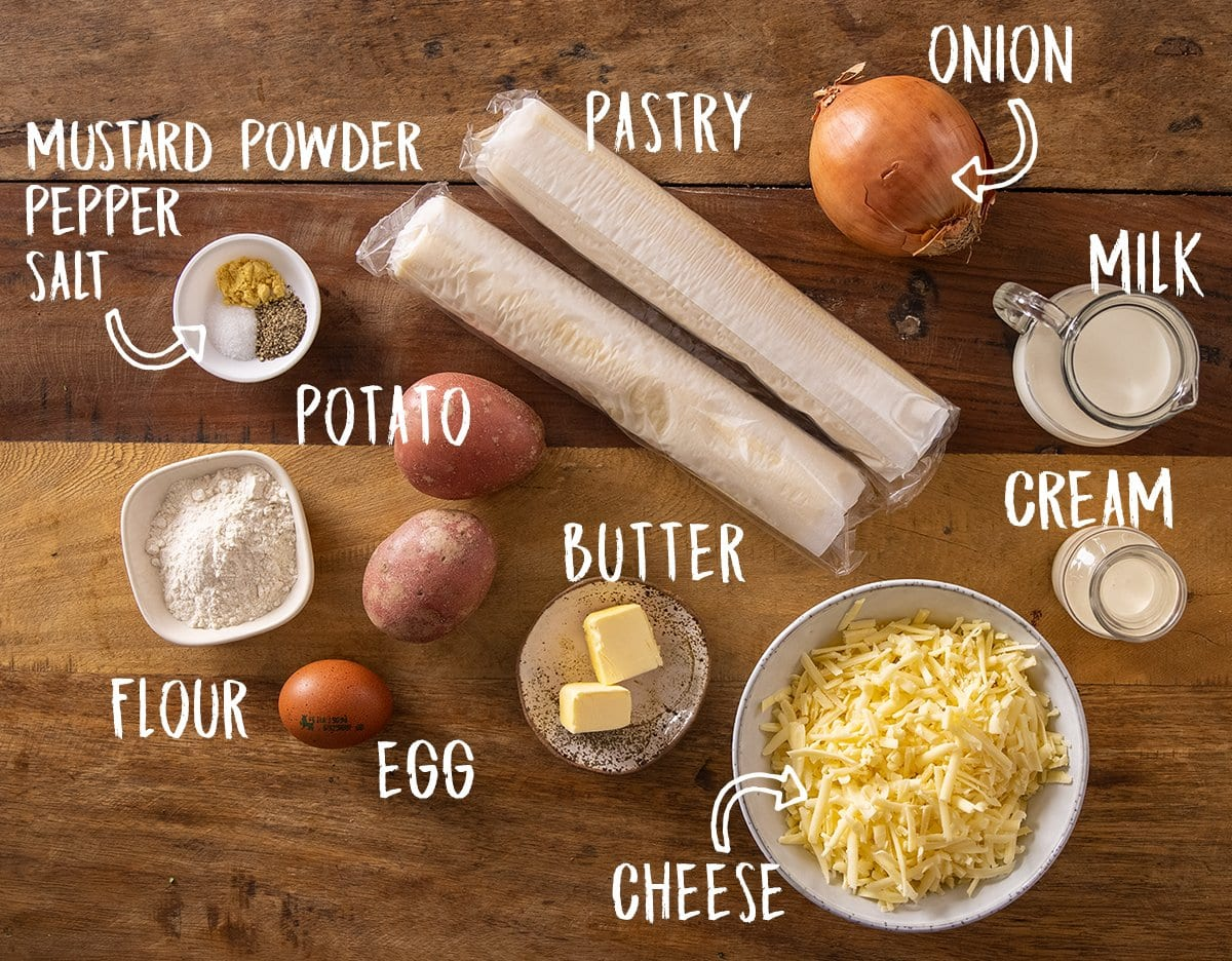 Ingredients for individual cheese and onion pies on a wooden table
