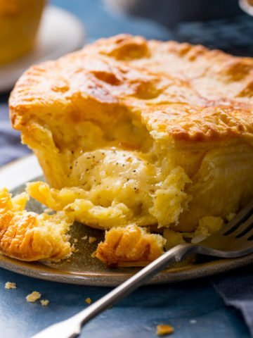 Square image of a small cheese and onion pie on a plate with a piece taken out.