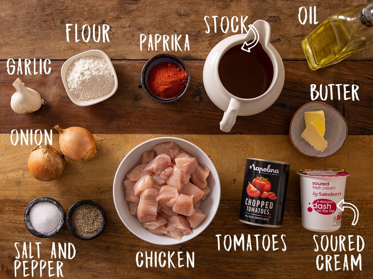Ingredients for chicken paprikash on a wooden table.