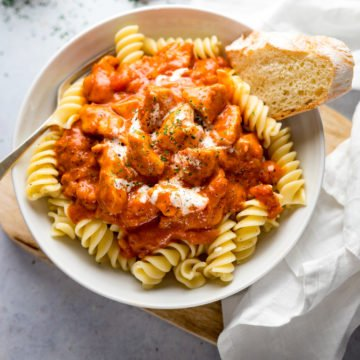 Chicken Paprikash in a white bowl on top of pasta with a piece of bread in the bowl.