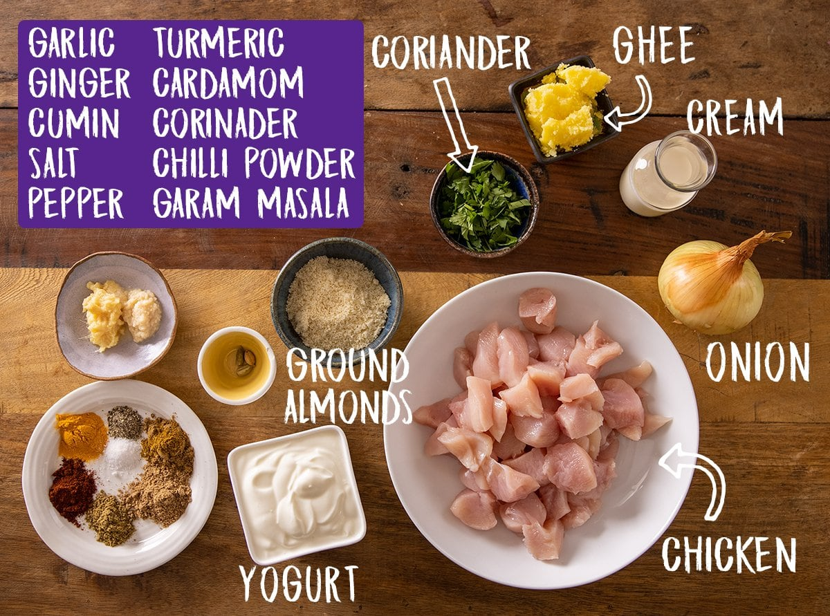 Ingredients for chicken pasanda on a wooden table.