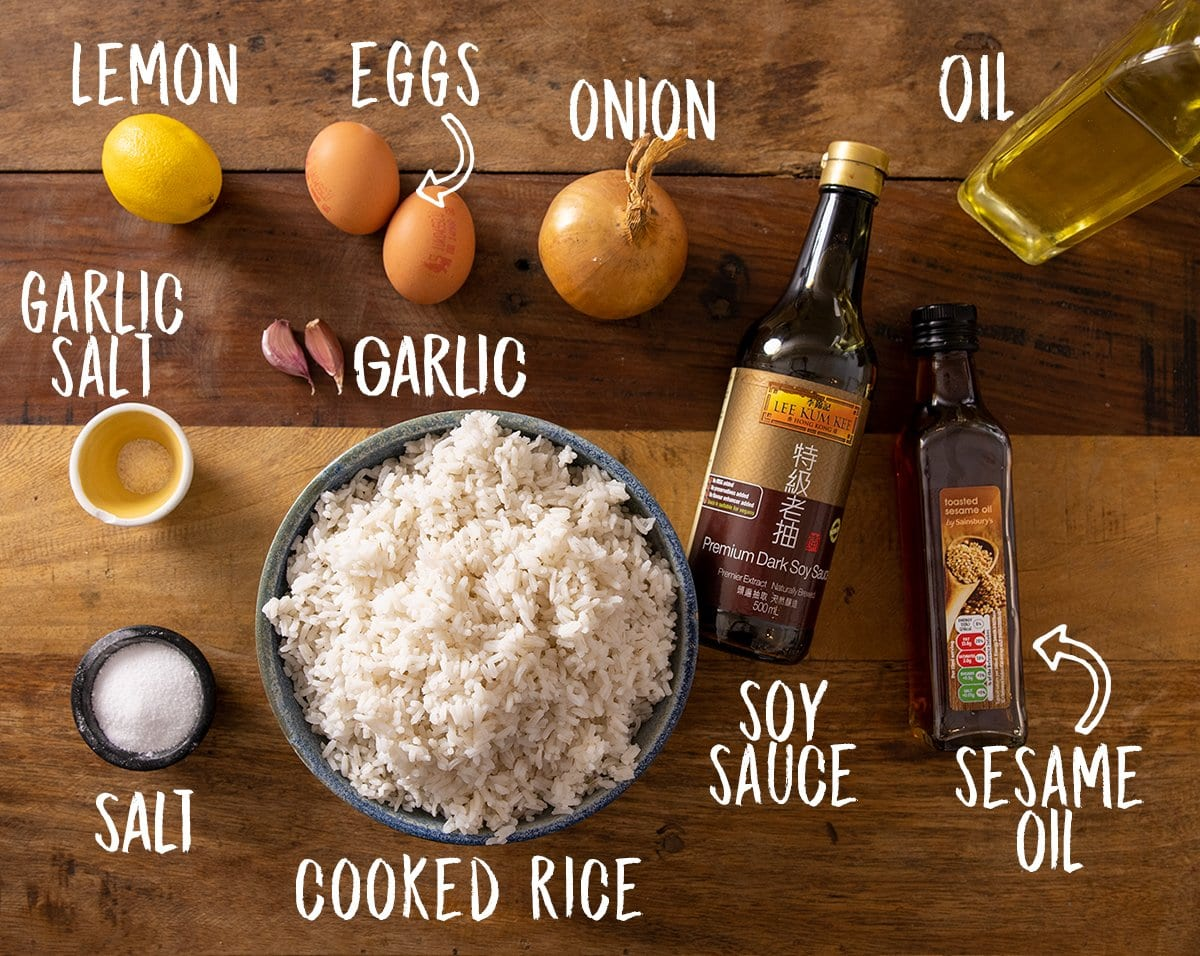 Ingredients for egg fried rice on a wooden table.