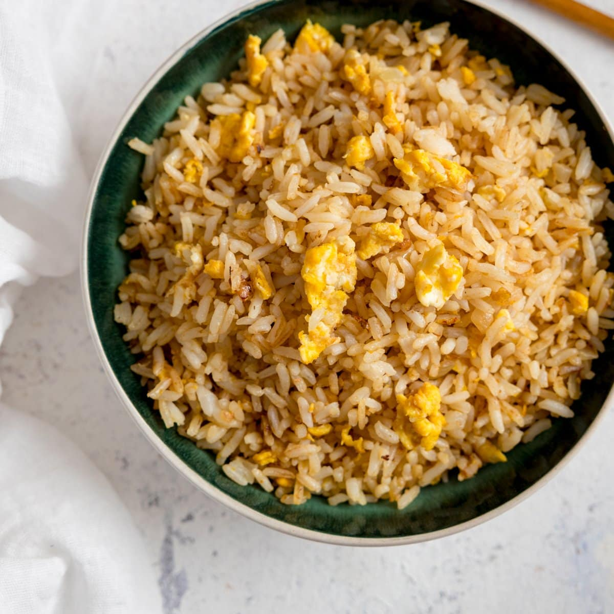 Egg fried rice on a dark bowl on a white background.