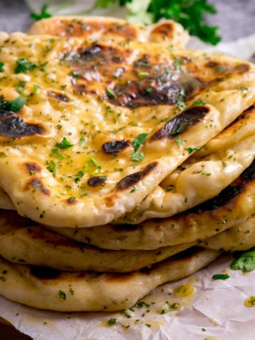 Pile of garlic naan breads on a piece of parchment on top of a wooden board.