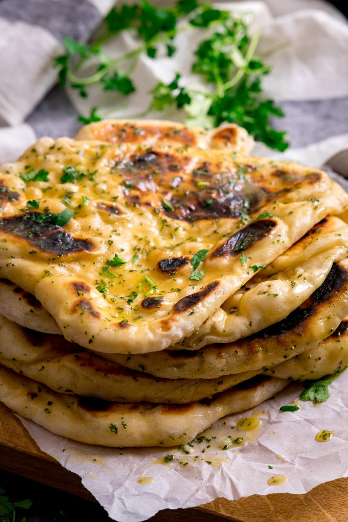 Pile of garlic naan breads on a light background. Fresh herbs in the background.
