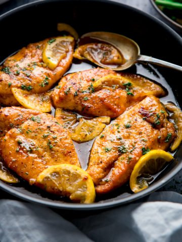Square image of a dark pan filled with honey lemon chicken.
