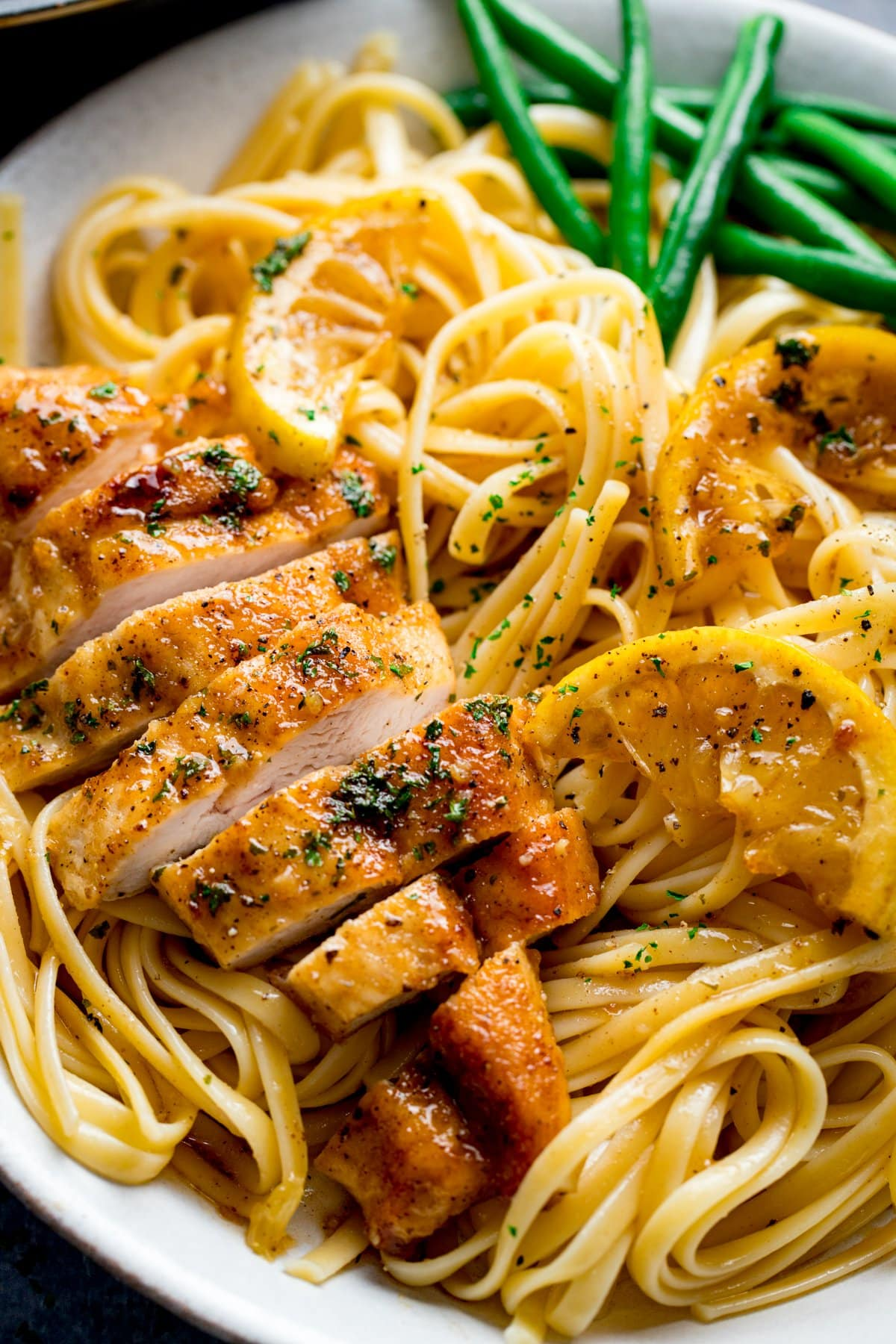 Sliced honey lemon chicken breast on a plate of linguine with green beans.