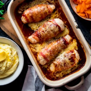 Square image of hunters chicken in a baking dish next to side dishes of mashed potatoes, carrots and green beans.