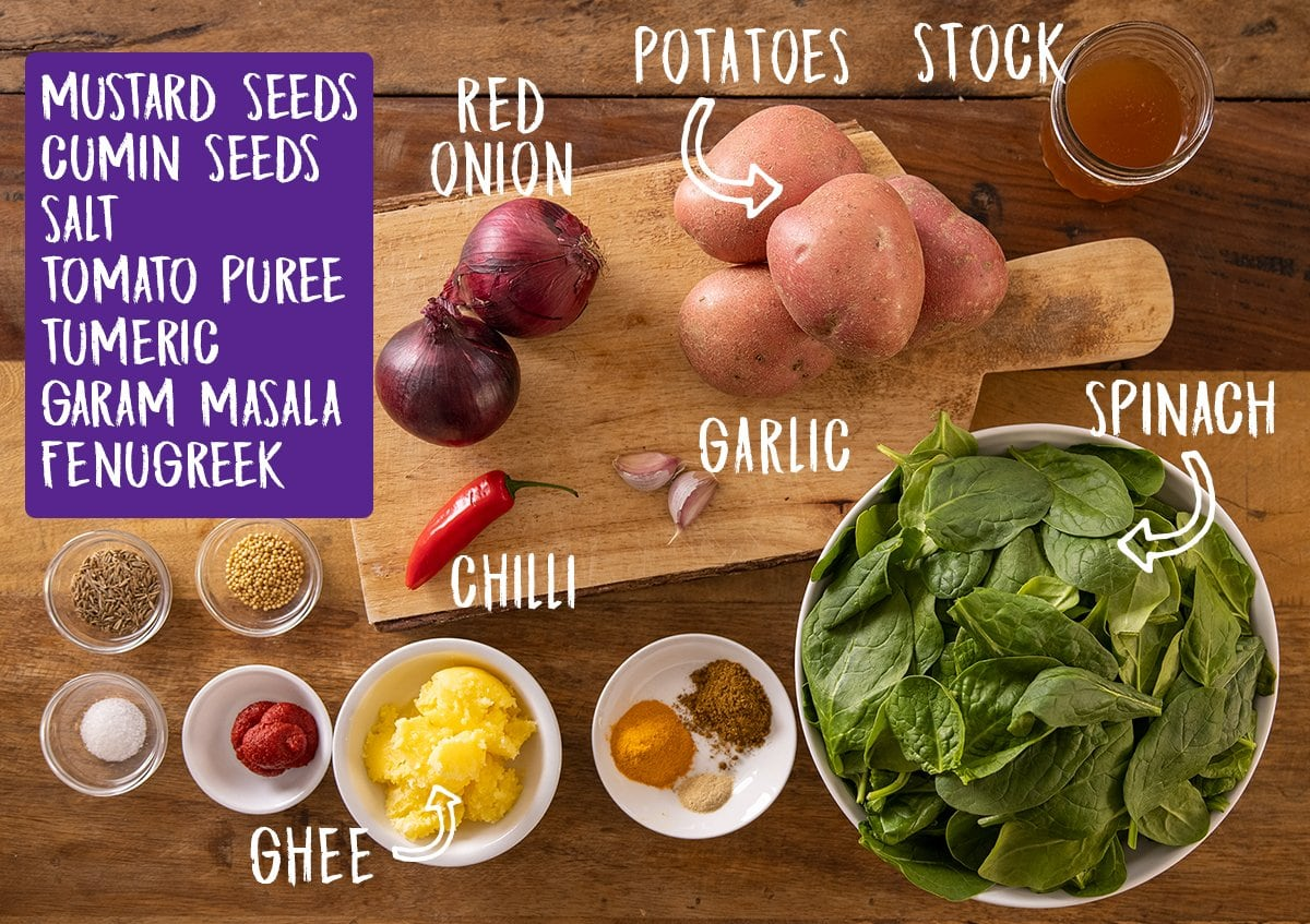 Ingredients for saag aloo on a wooden table