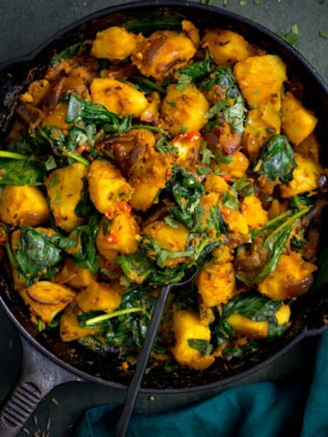 saag aloo in a black pan on a dark background