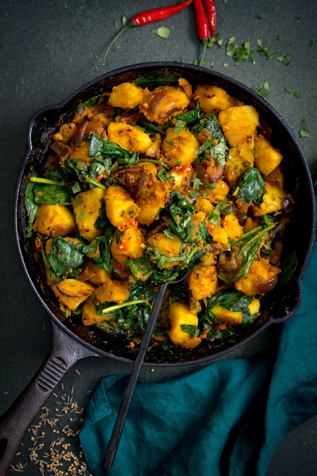 A spoonful of saag aloo being taken from a pan. The pan is on a dark green background.