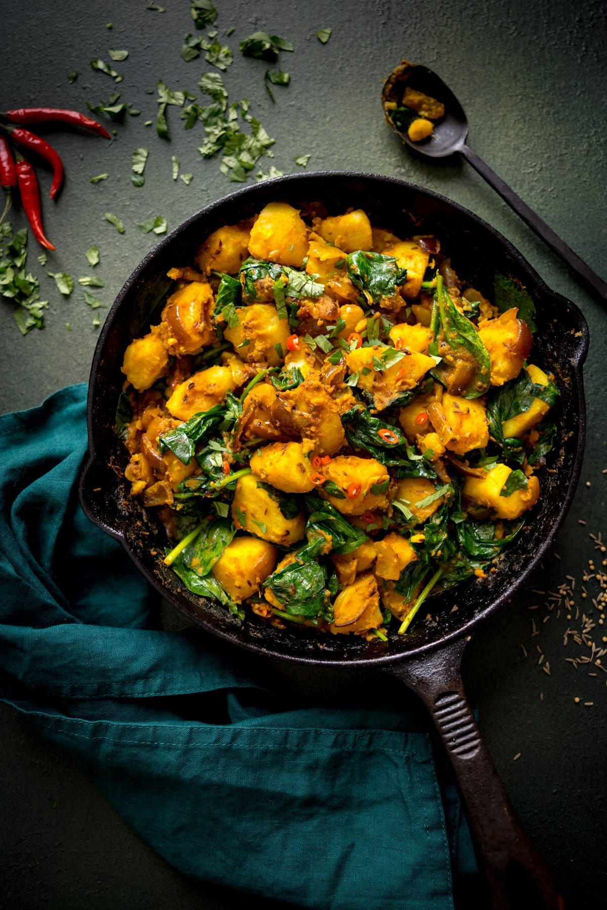 saag aloo in a cast iron pan on a dark green background/ Green napkin, a black spoon and garnishes surround the pan.