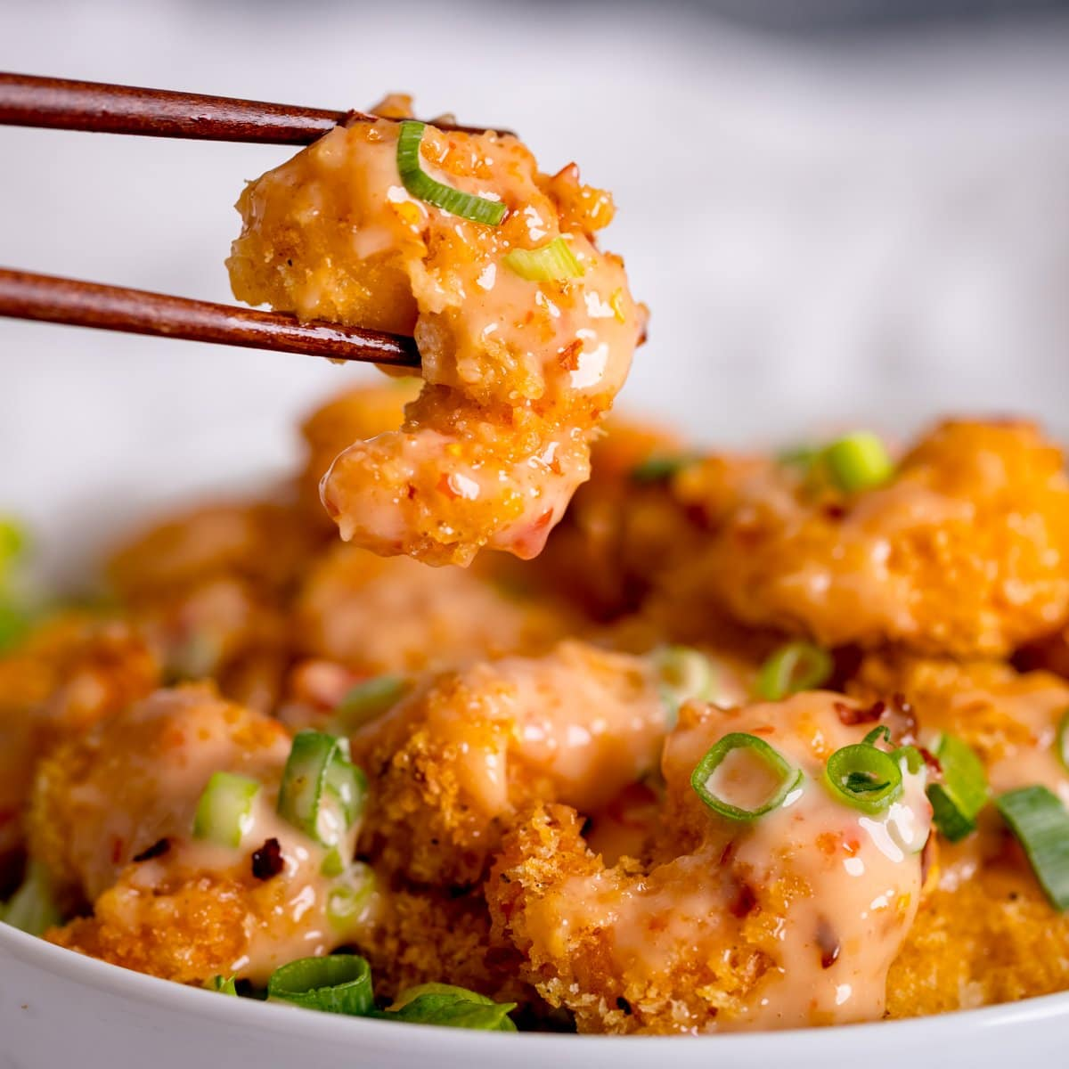 Crispy shrimp being lifted out of a bowl with chopsticks. Shrimp is covered with bang bang sauce.