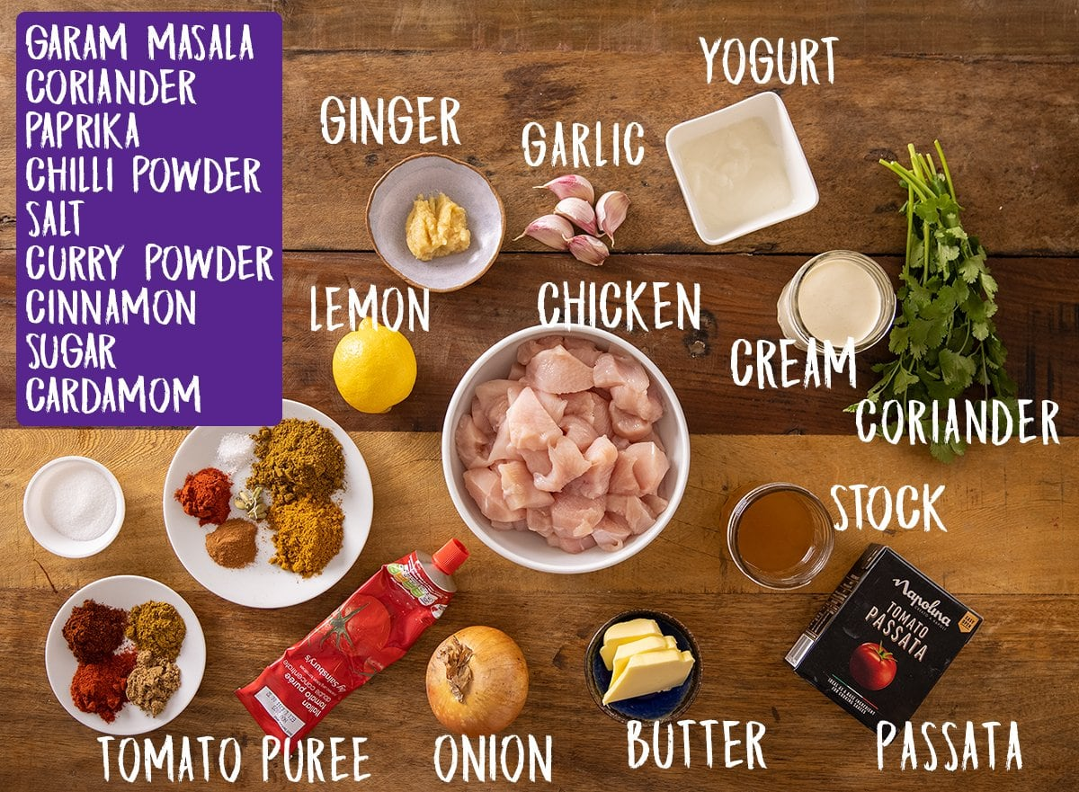Ingredients for butter chicken curry on a wooden table
