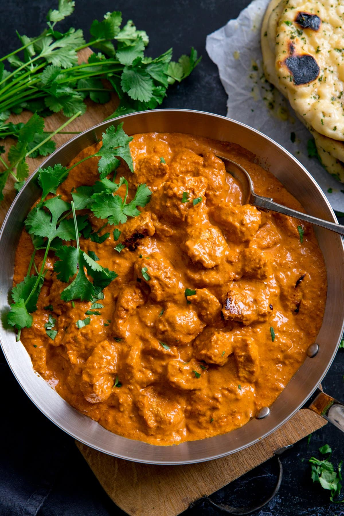 Overhead image of a pan filled with butter chicken curry, topped with fresh coriander. Naan bread just in shot.
