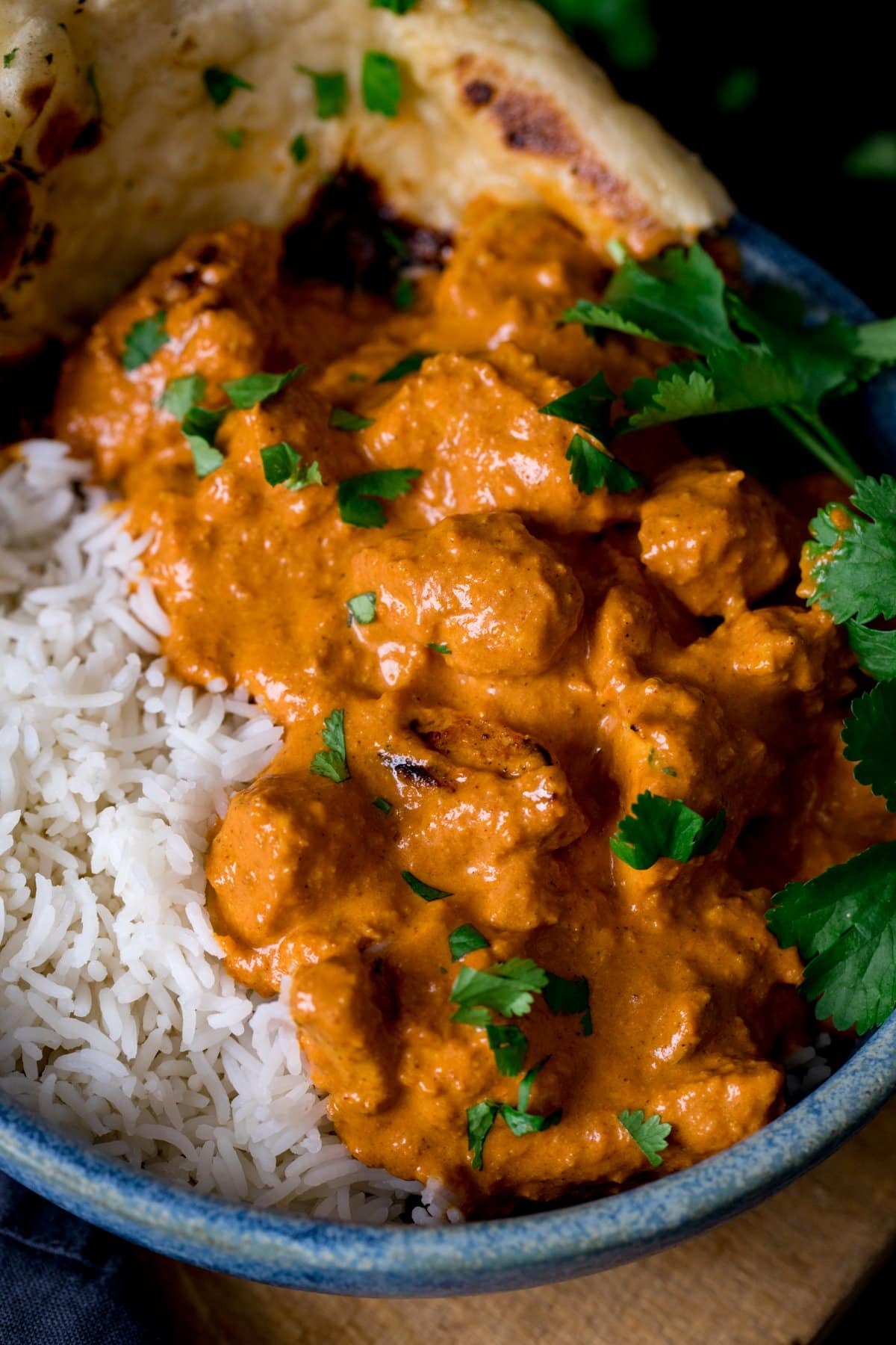 Butter chicken in a bowl with rice and naan bread.