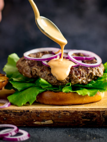 Burger sauce being drizzled from a spoon onto an open burger