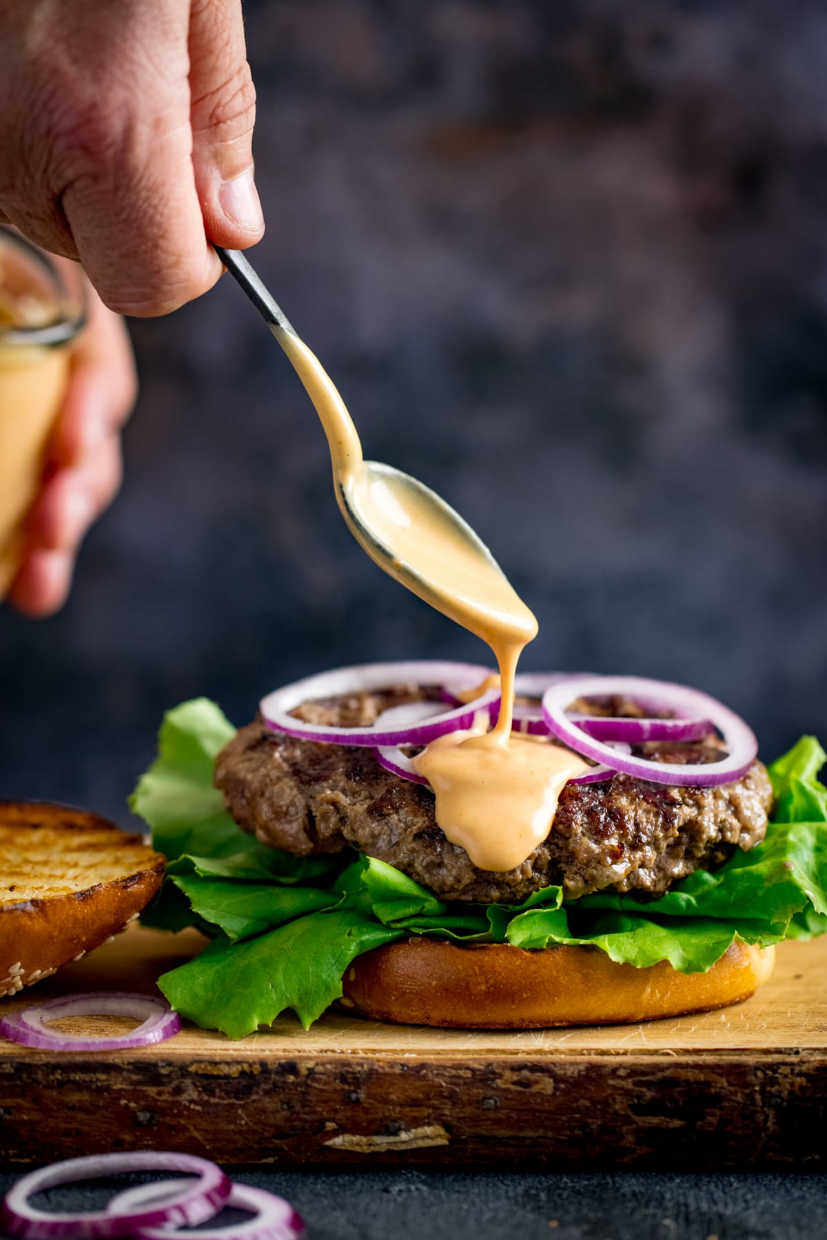 Burger sauce being drizzled from a spoon onto an open burger.