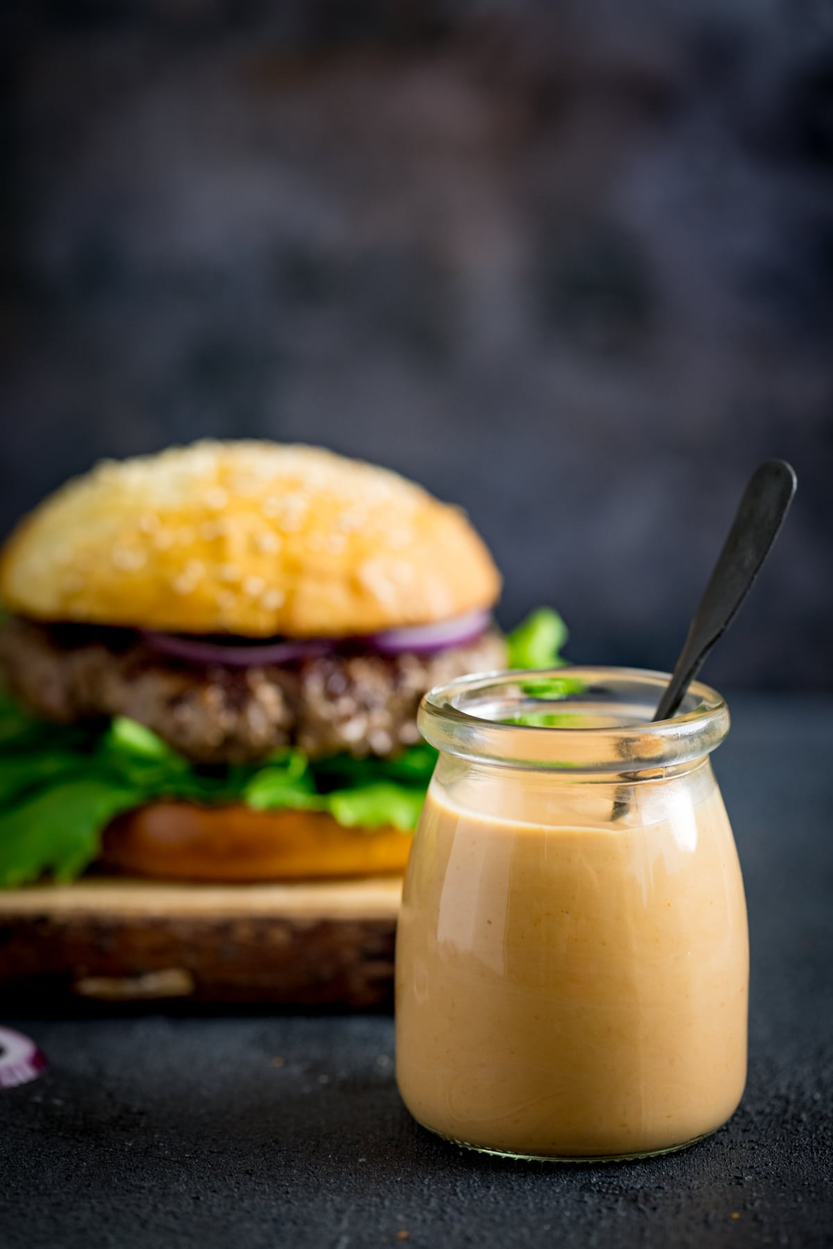 Burger sauce in a glass jar against a dark background. There is a burger in the background.
