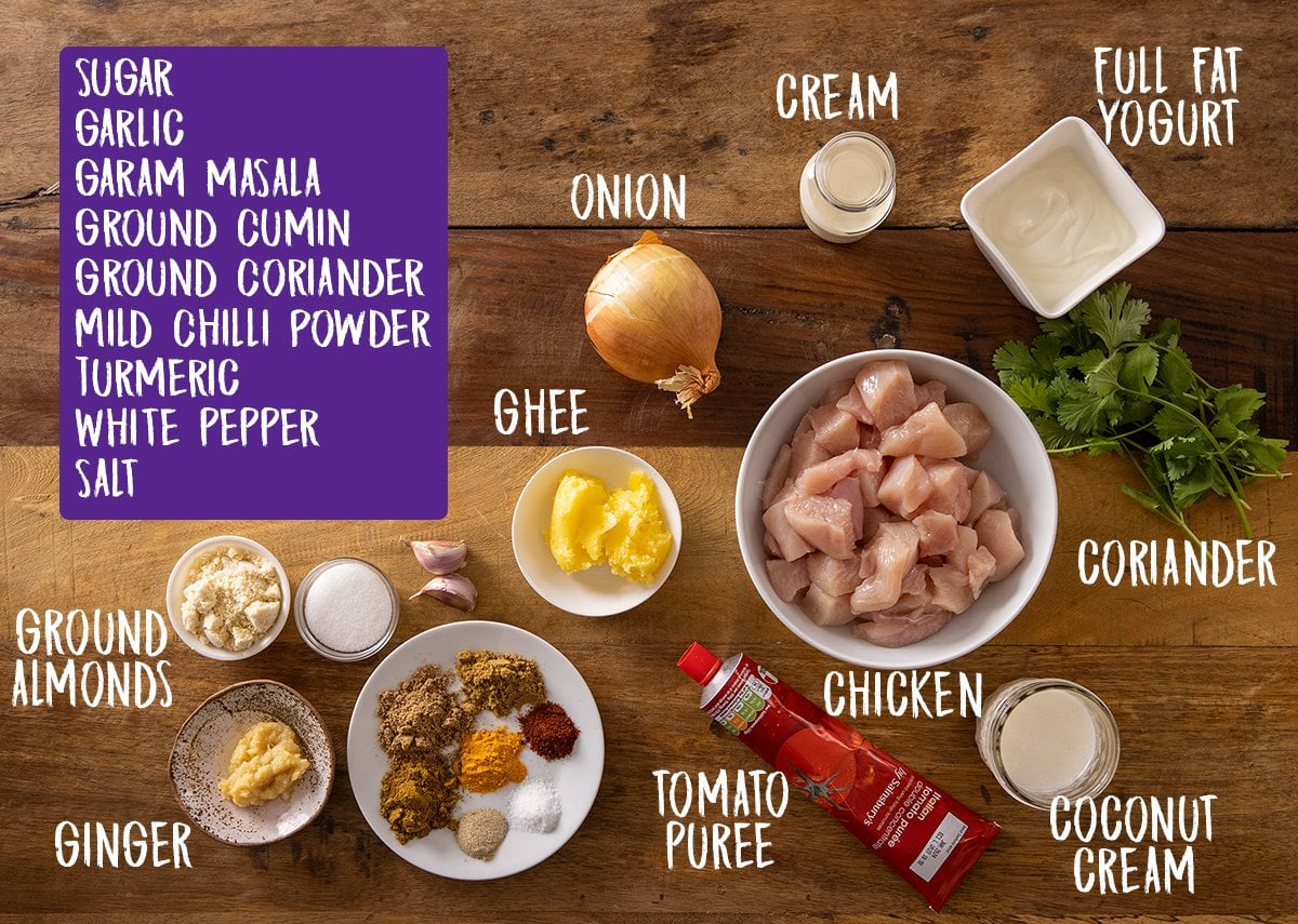 Ingredients for chicken korma on a wooden table.
