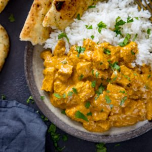 Chicken korma, naan and rice in a bowl on a dark background.