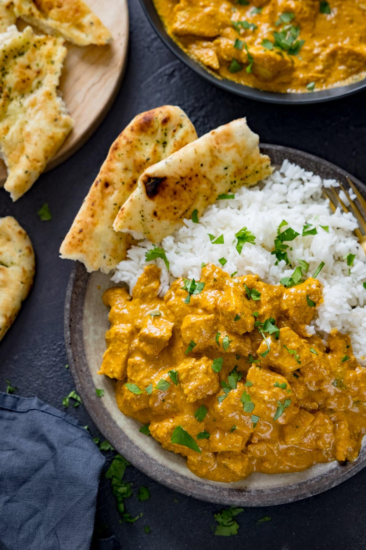 Chicken korma, rice and naan in a bowl on a dark background. Further bowl of curry and naan in background.