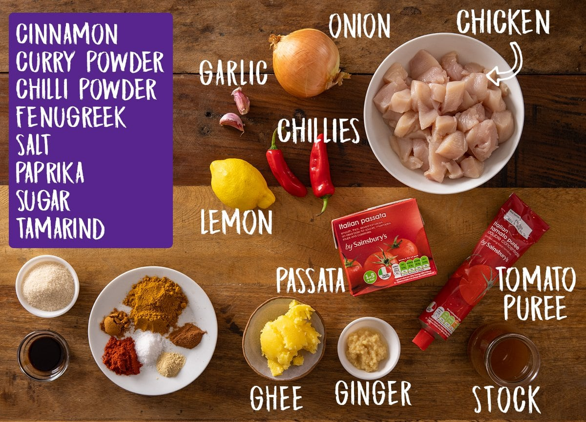 Overhead picture of ingredients for Chicken Pathia Curry on a wooden table.
