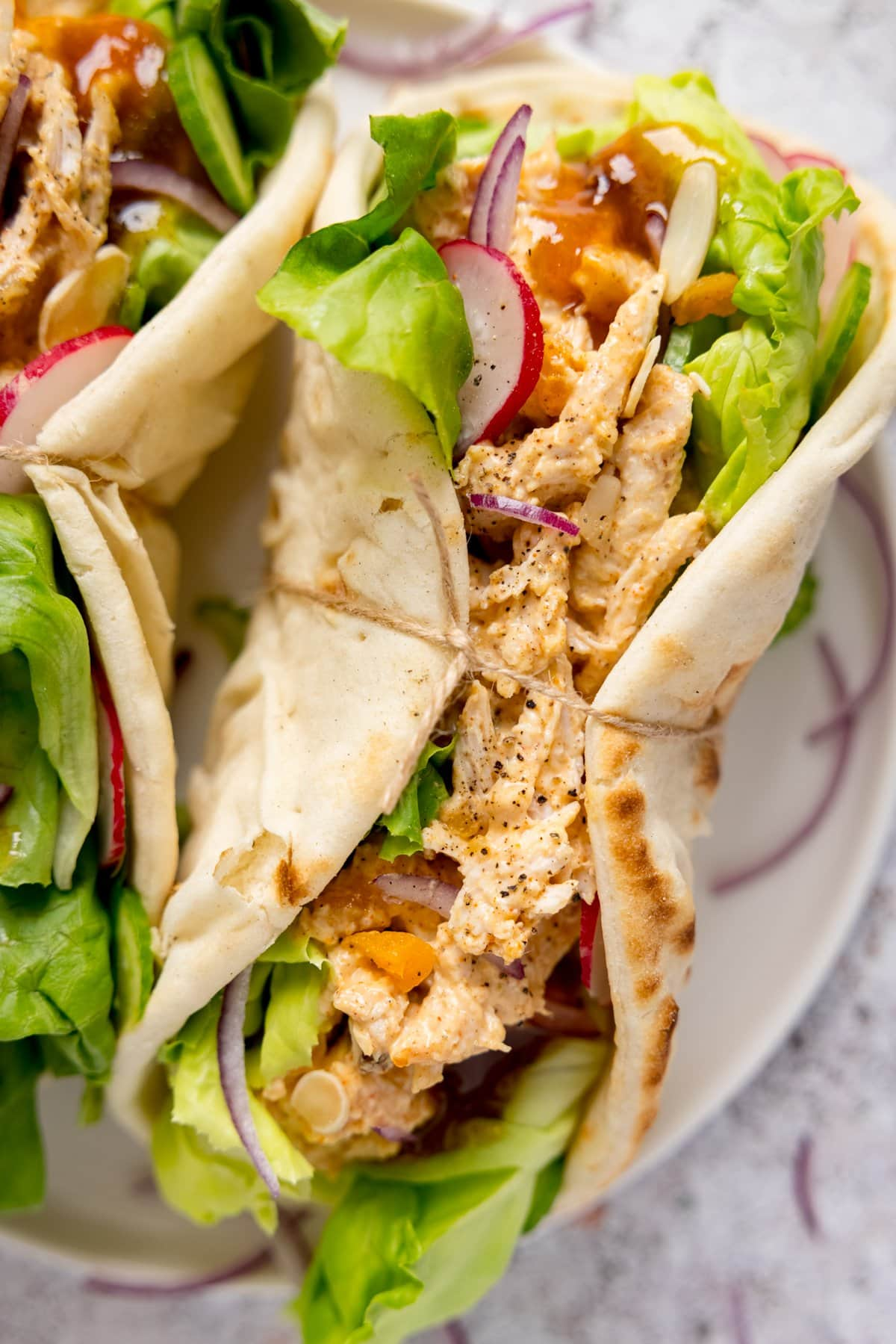 Coronation chicken and salad in a wrap with a piece of string around it. The wrap is on a light plate, next to a further wrap, on a light background.